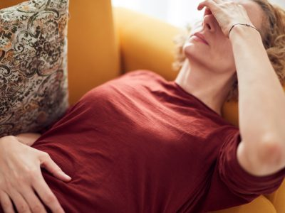 Woman with sinus pain, headache and stomach problems, lying on a couch at home.
